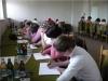 Uczestnicy spotkania siedzący przy oknach zajęci rozwiązywaniem testów