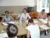 Uczestniczki warsztatów siedzą przy stole podczas pracy z załączonymi materiałami szkoleniowymi