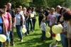 Uczestnicy spotkania stojący z dziecmi w dwóch kolejkach na trawie