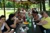 Uczestniczki Programu Aktywności Lokalnej w Sielcu wraz rodzinami siedzą w plenerze przy stole w piknikowej atmosferze